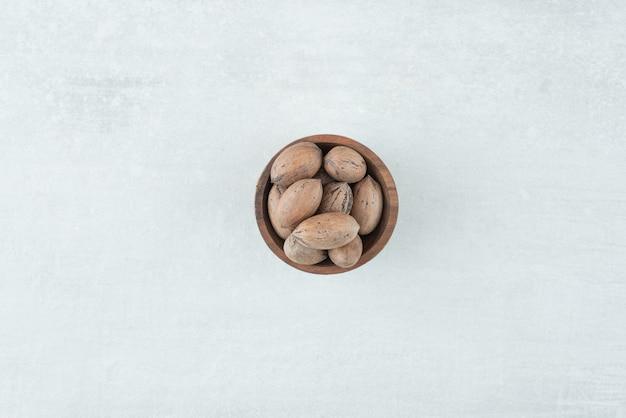 Uma pequena tigela de madeira com nozes em fundo branco. foto de alta qualidade