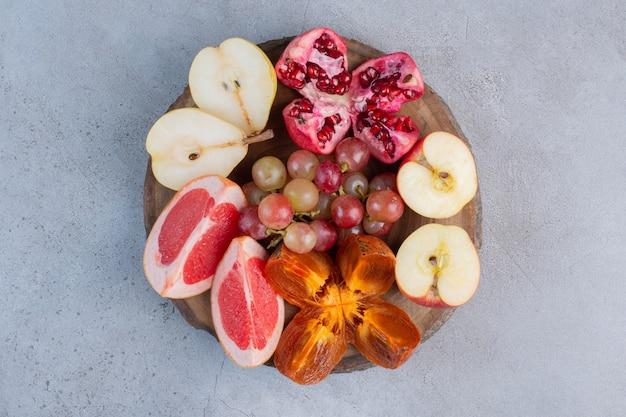Uma pequena variedade de frutas em uma placa de madeira com fundo de mármore.
