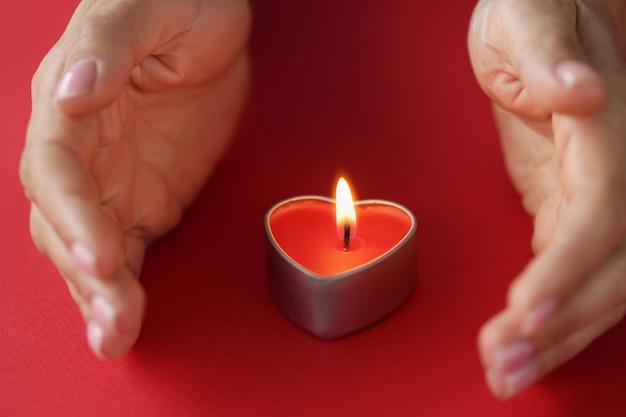 Uma pequena vela perfumada queima nas mãos de uma mulher, mantendo o conceito de casa quente e aconchegante
