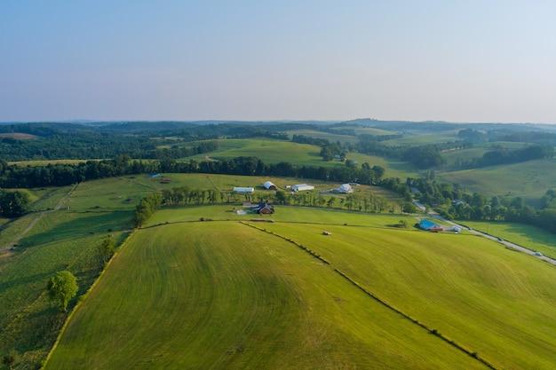 Uma pequena vila de bentleyville atrás de árvores e colinas no prado agrícola na pensilvânia, eua