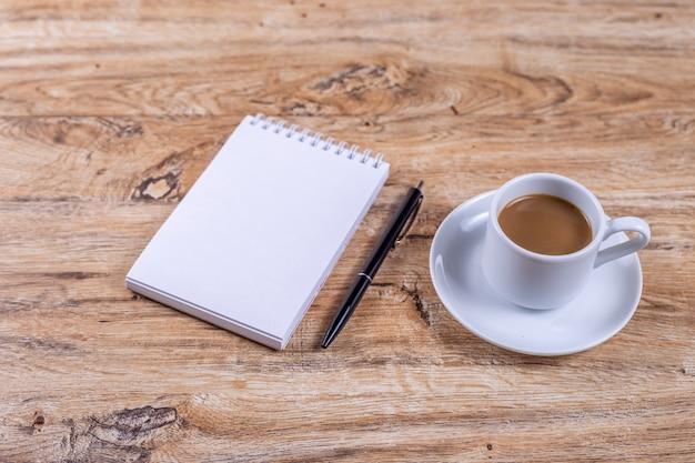 Uma pequena xícara de café branca em um pires fica em uma mesa de madeira ao lado de um caderno e uma caneta