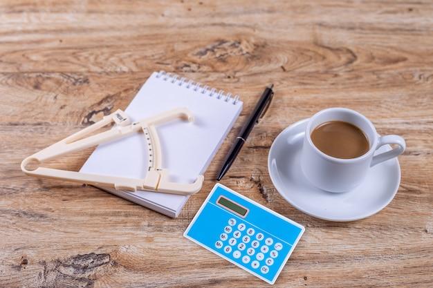 Uma pequena xícara de café em um pires está em uma mesa de madeira ao lado de um caderno