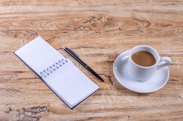 Uma pequena xícara de café em um pires fica em uma mesa de madeira ao lado de um caderno e uma caneta