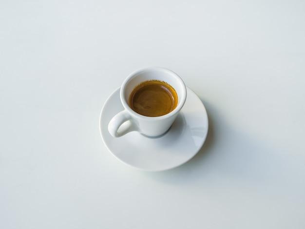 Uma pequena xícara de café preto forte sobre uma mesa branca.