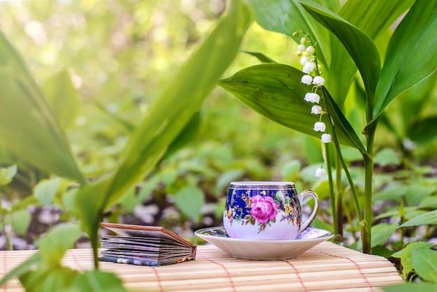 Uma pequena xícara de chá ao lado das flores dos lírios do vale