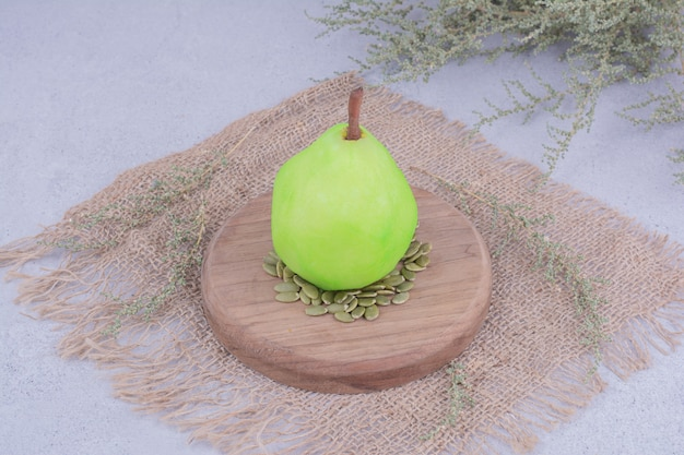 Uma pêra verde em uma placa de madeira com sementes de abóbora