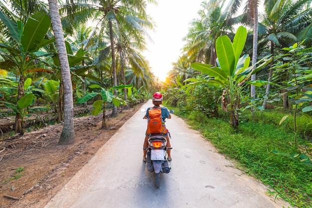 Uma pessoa andando de bicicleta no circuito de moto de ha giang, motociclistas famosos do destino de viagem, pilotos fáceis. paisagem da montanha do geopark do cársico do ha giang no vietname norte. estrada sinuosa em um cenário deslumbrante.