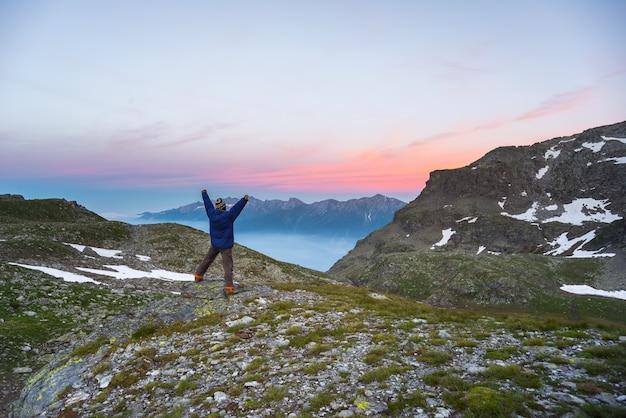 Uma pessoa assistindo o nascer do sol no alto dos alpes