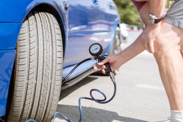 Uma pessoa bombeia os pneus das rodas do carro com um compressor com manômetro