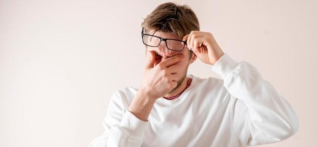 Uma pessoa cansada de usar óculos, sente desconforto, dor, estresse no escritório
