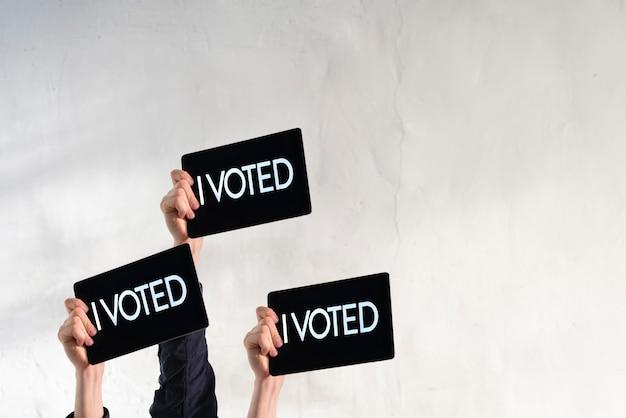 Uma pessoa com a mão levantada com placa preta e texto eu votei na eleição pela democracia