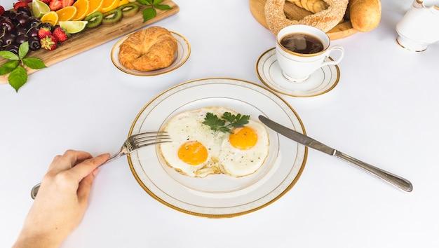 Uma pessoa comer omelete de ovo frito com garfo