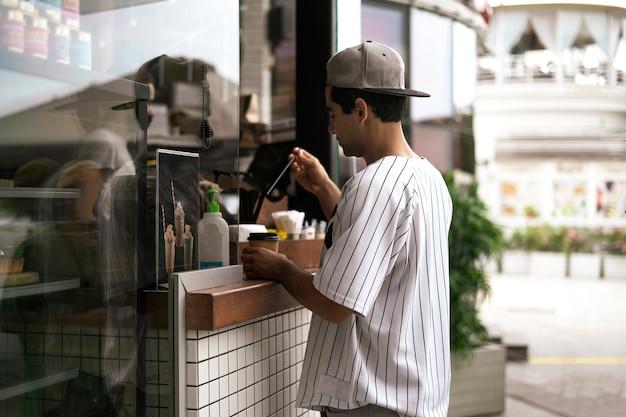 Uma pessoa comprando comida e café em um café de rua da cidade