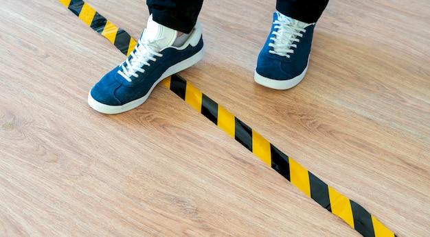 Uma pessoa cruza a linha de parada preta e amarela, freando o conceito de limite