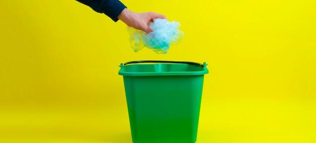 Uma pessoa deixa cair o lixo na lata de lixo