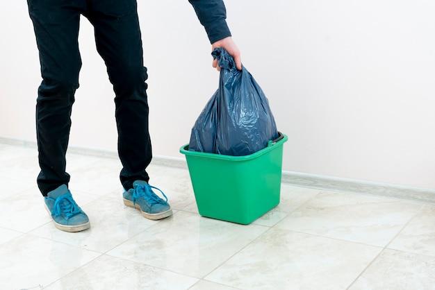 Uma pessoa deixa cair o lixo na lata de lixo Foto Premium