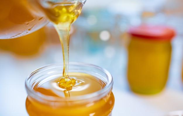 Uma pessoa desconhecida derrama mel dourado doce em potes transparentes e limpos, em pé sobre uma grande mesa de madeira branca em um dia ensolarado