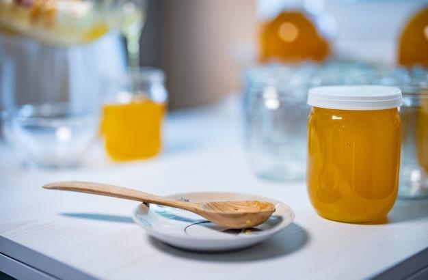 Uma pessoa desconhecida derrama mel dourado em potes transparentes e vazios sobre uma grande mesa de madeira branca em um dia ensolarado