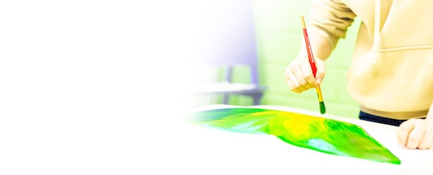 Uma pessoa desenha com um pincel e pinta em uma grande tela em um estúdio de arte. criativo, moderno artista de belas-artes, uma obra-prima do desenho, treinamento em desenho, escola de arte, cursos de desenho à distância, banner