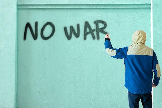 Uma pessoa do sexo masculino escreve com tinta spray pode a declaração de parar a guerra na parede, conceito de símbolo de graffiti