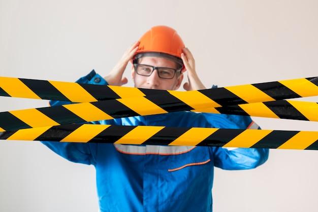 Uma pessoa do sexo masculino inicia a linha de fita preta e amarela, zona de proteção