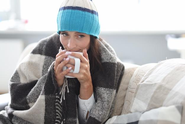 Uma pessoa doente bebe um líquido quente.