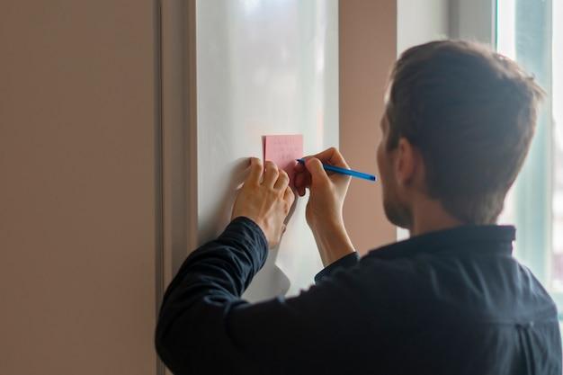 Uma pessoa escreve um lembrete no adesivo na geladeira
