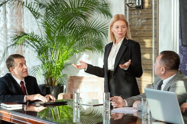 Uma pessoa falando com colegas em uma reunião de trabalho na sala de reuniões