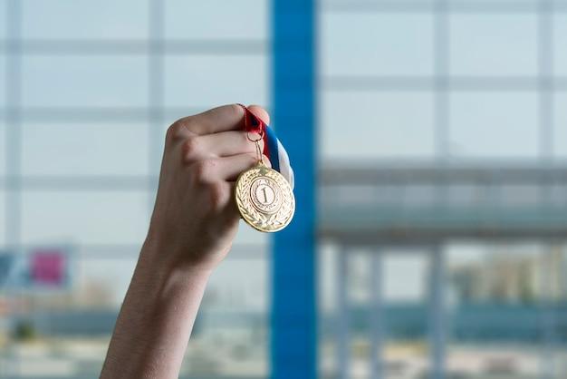 Uma pessoa levantou a mão ganhando o primeiro lugar, segurou a medalha de ouro