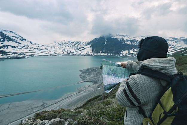 Uma pessoa olhando para o mapa de trekking, céu dramático ao entardecer, lago e montanhas nevadas, sentimento frio nórdico