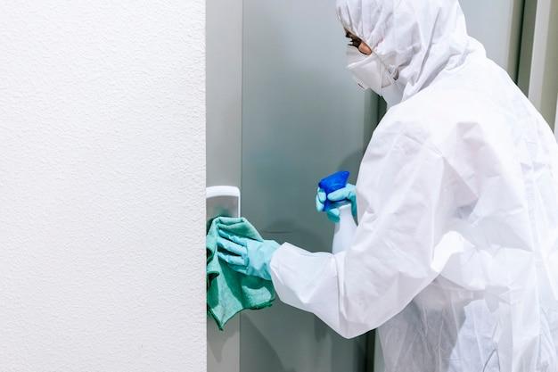 Uma pessoa protegida com roupas de segurança contra uma pandemia ou vírus, limpa e desinfeta o portal de uma casa