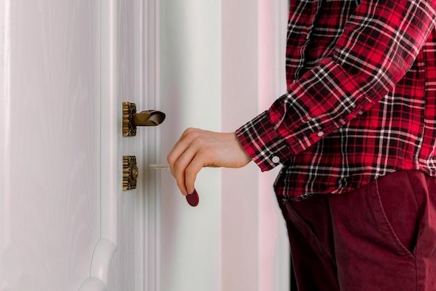 Uma pessoa próxima chega em casa e abre a porta com as chaves