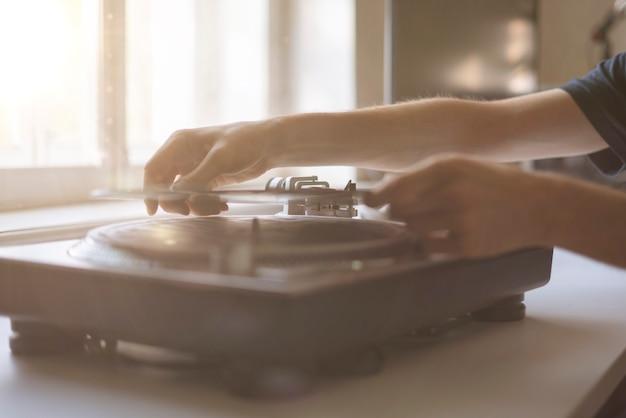 Uma pessoa próxima colocou a agulha em um disco tocando vinil na festa