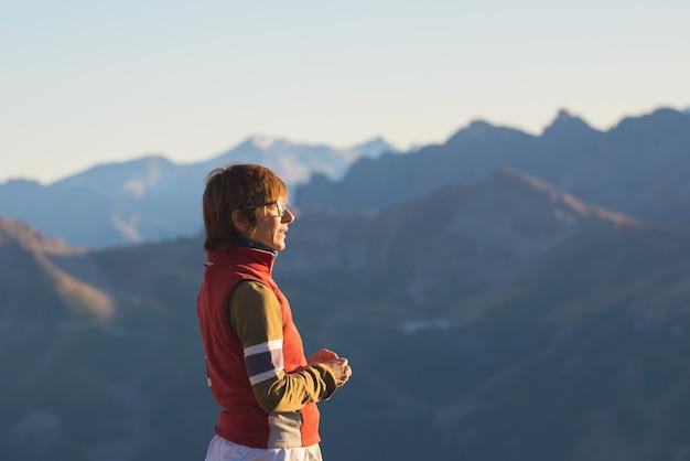 Uma pessoa que olha a vista majestosa de picos de montanha de incandescência no por do sol altamente acima nos cumes. vista traseira, imagem tonificada e filtrada