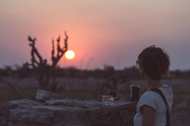 Uma pessoa que tem uma bebida e que olha o por do sol colorido no deserto de namib, viaja destino em namíbia, áfrica. conceito de aventura e pessoas viajando.