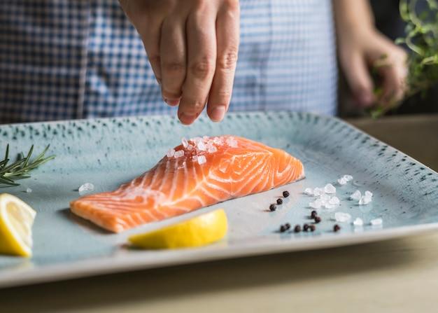 Uma pessoa que tempera um filé de salmão comida fotografia receita idéia