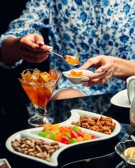 Uma pessoa que toma confiture amarelo da mesa de chá com doces e nozes.
