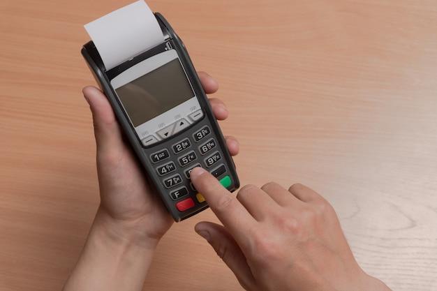 Uma pessoa segura na mão um terminal para pagar compras em uma loja usando cartões bancários ou nfc