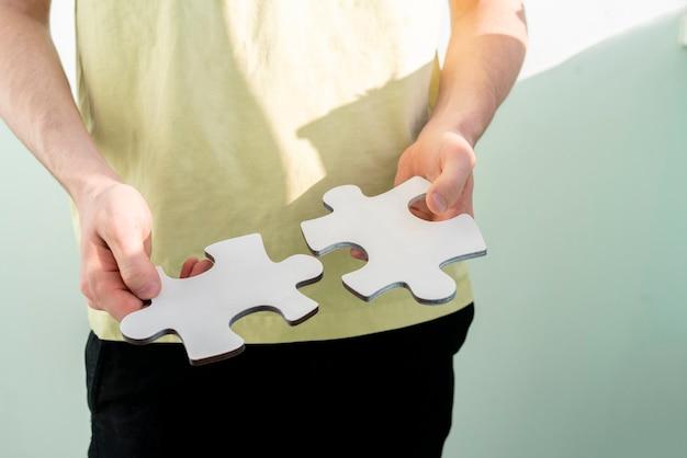 Uma pessoa segurando e conectando pizzles quebra-cabeças, resolvendo o problema