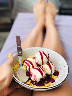 Uma pessoa segurando um prato de sorvete