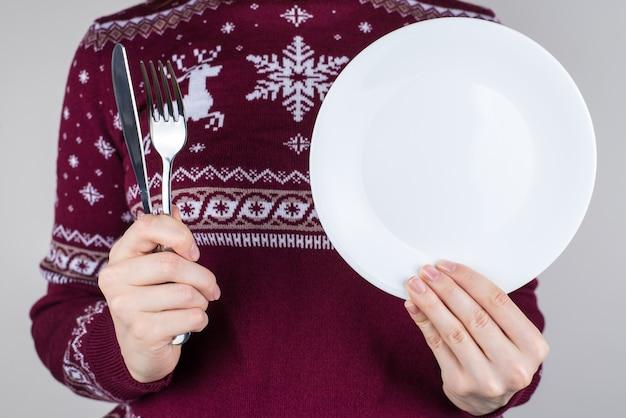 Uma pessoa segurando um prato sem comida nele