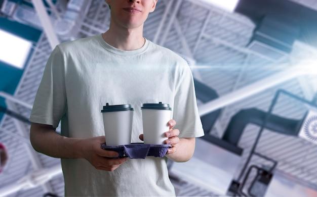 Uma pessoa segurando uma bandeja com dois copos de papel de café
