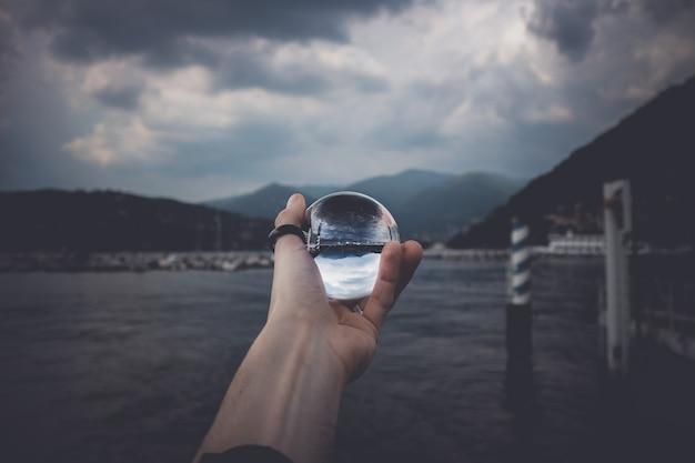 Uma pessoa segurando uma bola de cristal com o reflexo de montanhas altas e belas nuvens