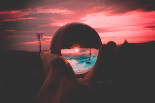 Uma pessoa segurando uma bola de vidro com o reflexo do céu colorido e o belo pôr do sol