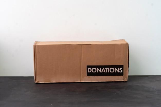 Uma pessoa segurando uma caixa de papelão com uma palavra de doação, entrega voluntária de caridade