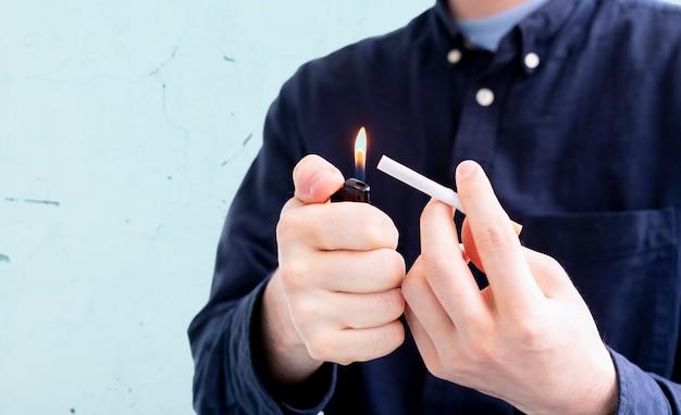 Uma pessoa segurando uma chama de isqueiro e um cigarro, fumando um habbit ruim
