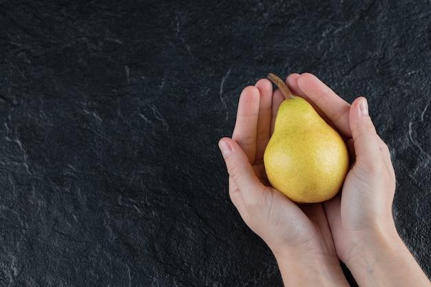 Uma pessoa segurando uma pêra amarela em ambas as palmas