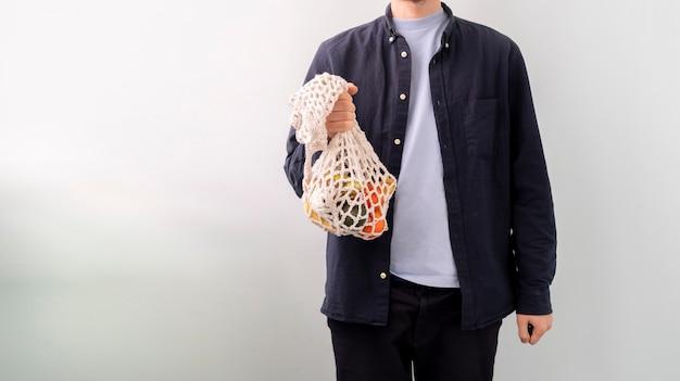 Uma pessoa segurando uma sacola de malha com frutas e vegetais frescos e crus, conversa ecológica e sem resíduos Foto Premium