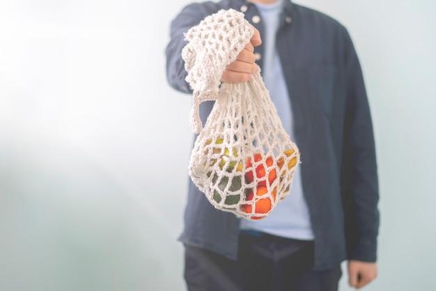 Uma pessoa segurando uma sacola de malha com frutas e vegetais frescos e crus, conversa ecológica e sem resíduos