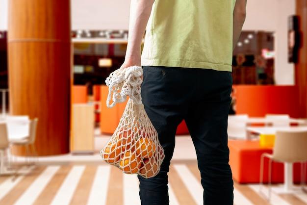 Uma pessoa segurando uma sacola ecológica de malha com alimentos de frutas frescas do supermercado